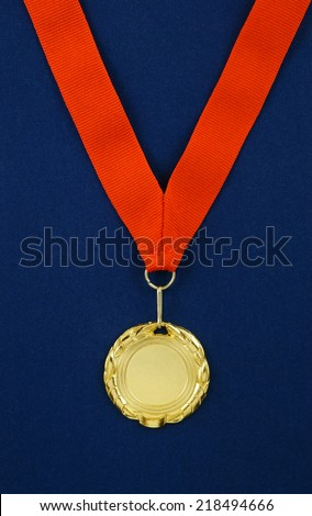 Gold medal with red ribbon on blue velveteen
