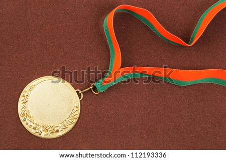 Gold medal with ribbon on brown velveteen - stock photo
