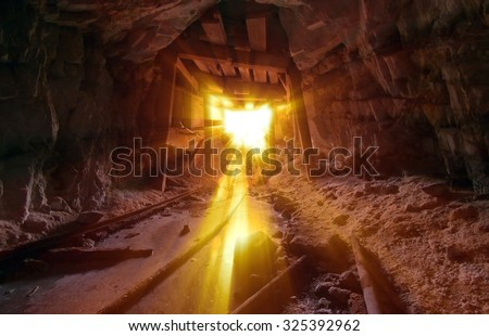 Gold Mine entrance with beams of light streaming in. - stock photo