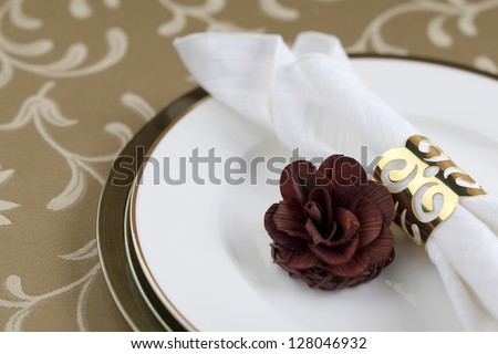 Gold napkin ring and flower decoration in a seamless background - stock photo