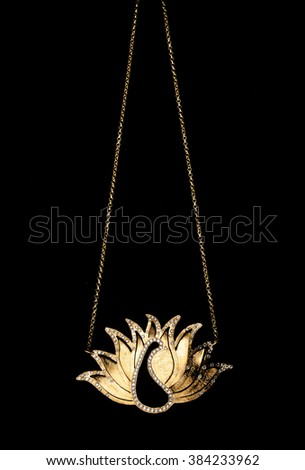 gold necklace with a ancient greek style on a black background - stock photo