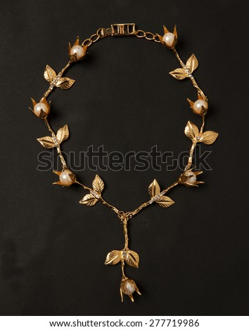 Gold necklace with golden leaves and flowers in black background - stock photo