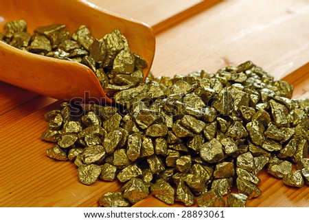gold nuggets and  scoop on wooden table - stock photo