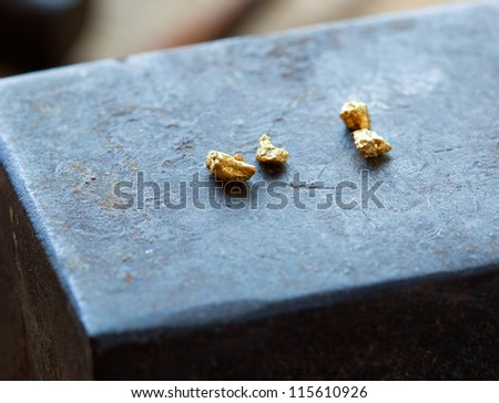 Gold nuggets on a old anvil. - stock photo