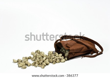 Gold nuggets spilling from a leather pouch.  Riches.  Wealth. - stock photo