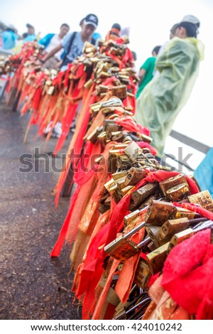 Gold padlocks and red ribbons at Gold Lock pass on Mount Hua or Hua shn, near Huayin in Shaanxi province. One of the Five Great Mountains of China, and has a long history of religious significance. - stock photo
