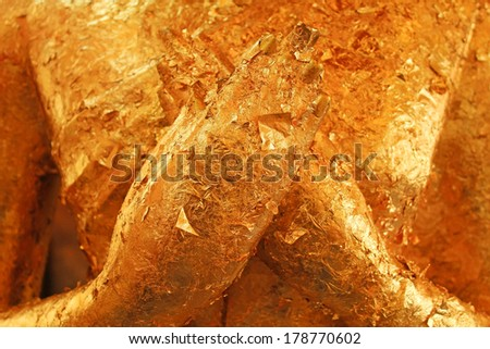 gold pallets and sheets on buddha's hand - stock photo