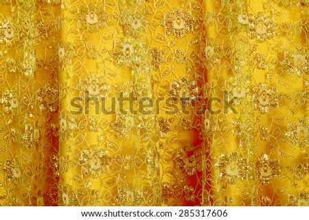 Gold peach lace sits on a gold silk background - stock photo