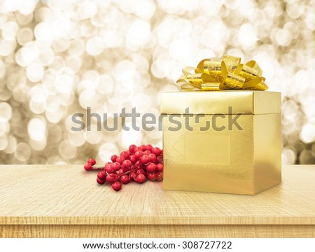 Gold present box and ribbon on wood table with sparkling gold bokeh light background, Holiday concept - stock photo