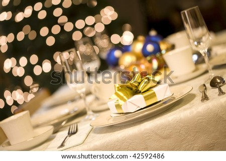 Gold present on dining table with Christmas tree lights in background - stock photo