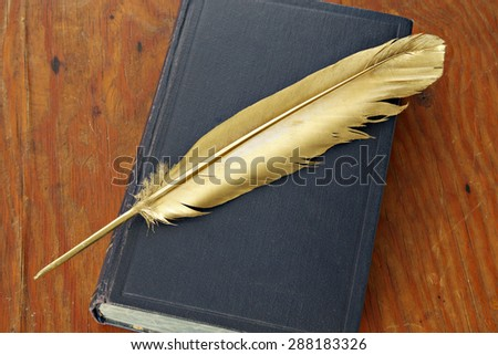 Gold quill pen and antiquarian book on grunge wood board - stock photo