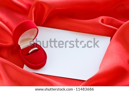Gold ring in box and empty card on red satin - stock photo