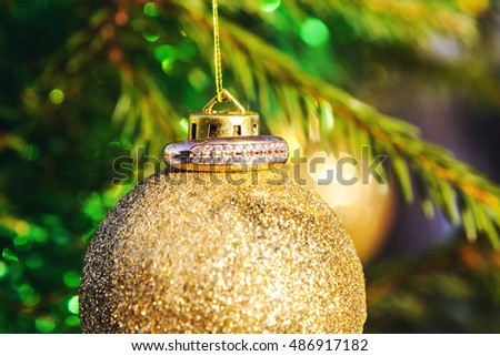 Gold ring on a gold Christmas tree ball, which hangs on a green Christmas tree.