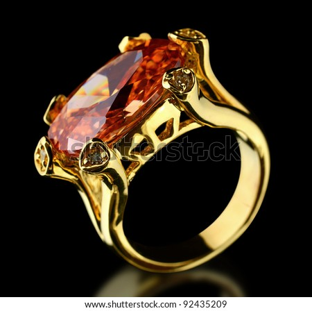 Gold ring with gem on black background - stock photo