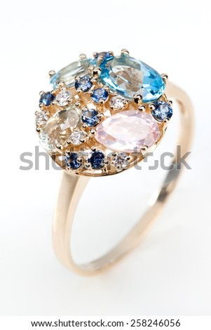 Gold ring with gems on white background - stock photo