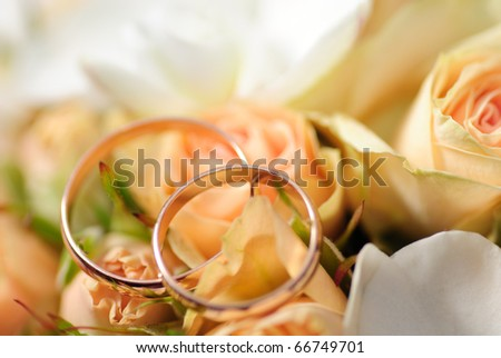 Gold rings on a bouquet of roses. Shallow DOF, selective focus. Weddinf postcard - stock photo