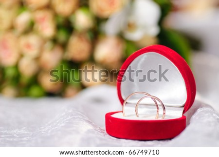 Gold rings on background of a bouquet of roses. Shallow DOF, selective focus - stock photo