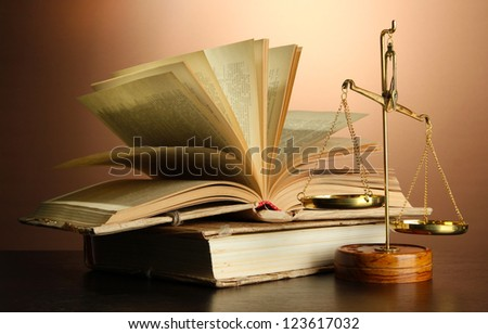 Gold scales of justice and books on brown background - stock photo