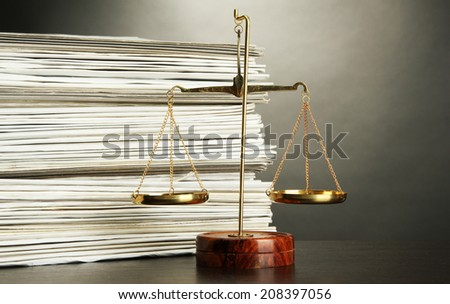 Gold scales of justice and folders on grey background - stock photo