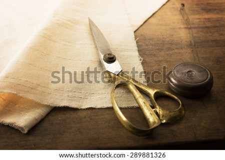 Gold scissors and natural white fabric. Measuring, cutting, sewing textile or fine cloth. Work table of a tailor. Shallow depth of field, Focus on scissors - stock photo