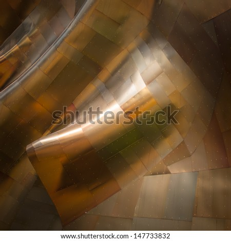 Gold sheet metal twists and curves to form a beautiful textured abstract background. - stock photo