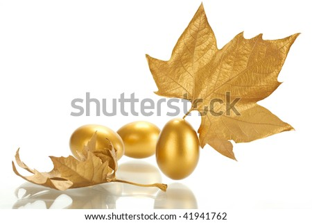 Gold sheet of a maple and gold egg on a white background.