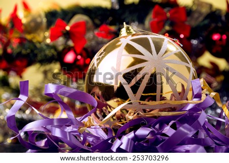 gold shiny Christmas ornament, placed on violet ribbon,Christmas tree at the background  - stock photo