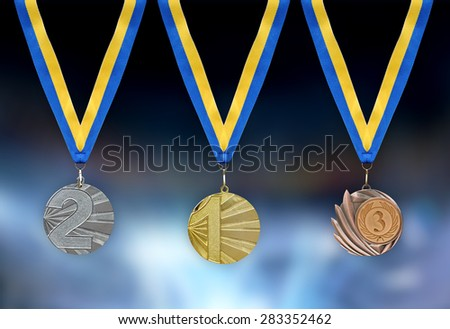 Gold, silver and bronze medals in the foreground with yellow blue ribbon - stock photo