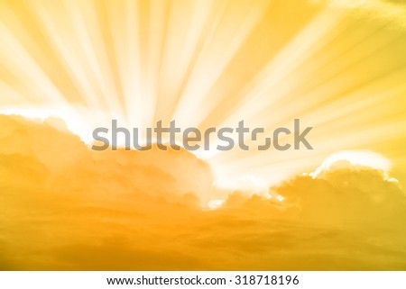 Gold sky and rays of light shining down with clouds atmospheric effect.