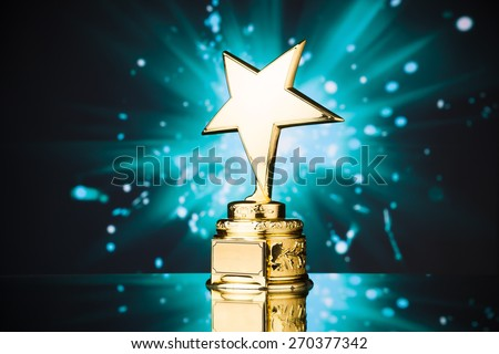 gold star trophy against blue sparks background - stock photo