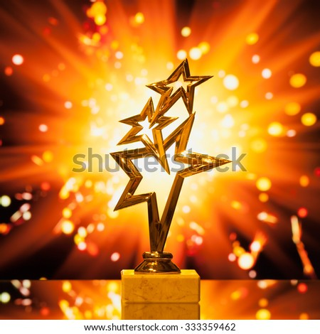 gold stars trophy against shiny sparks background - stock photo