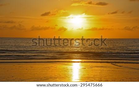 gold sunset sky on ocean beach - stock photo