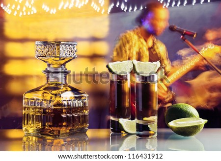 gold tequila and lime on a glass table in nightclub - stock photo