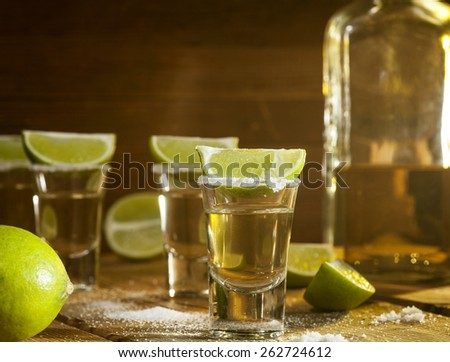 Gold tequila shots with lime fruits on wooden background - stock photo