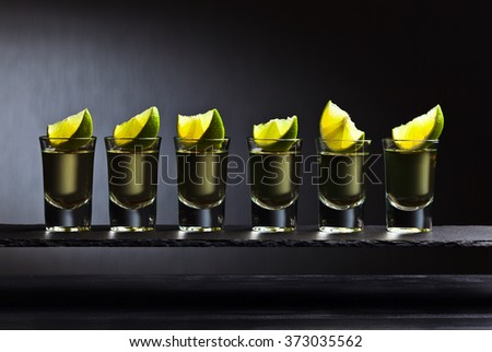 Gold tequila with lime on a dark background - stock photo