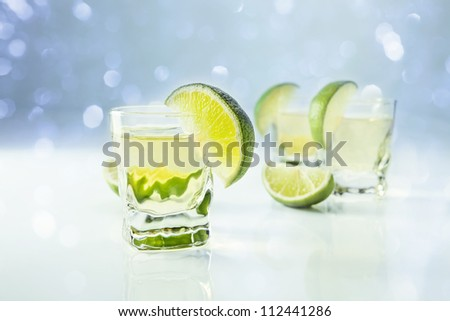 gold tequila with lime on a white reflective background - stock photo