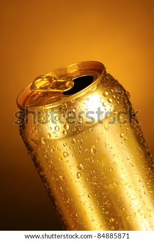 gold tin can on a yellow background. Focus on nearest water drops - stock photo