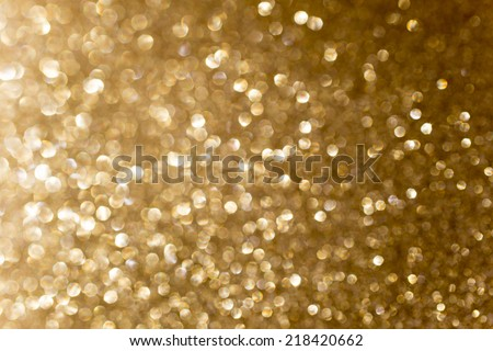Gold tone background of defocused glittering lights. - stock photo
