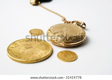 Gold watch and gold coins - stock photo