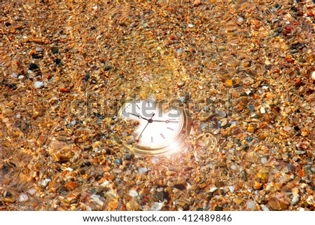 gold watch and sand of the sea on the coast - stock photo