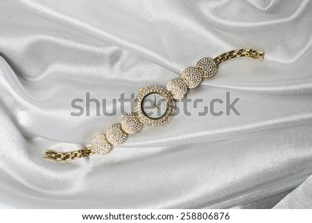gold watch on a silk background - stock photo