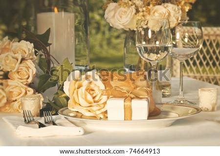 Gold wedding party favors on plate at reception - stock photo