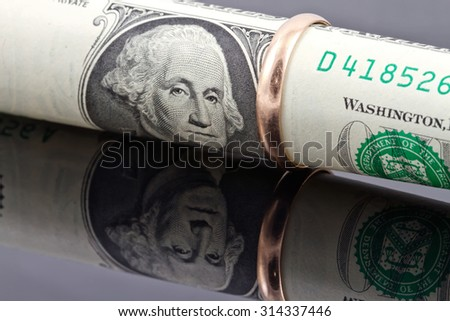 gold wedding ring dressed on the banknote one dollar - stock photo