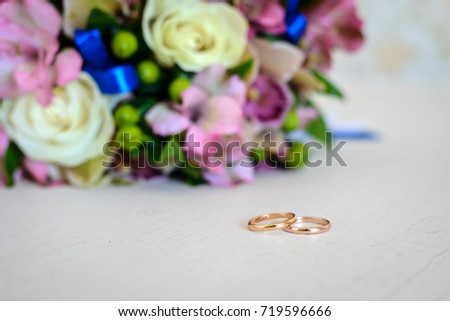 Gold Wedding Rings And Bouquet Of Colorful Flowers On A White Wooden Table In Rustic