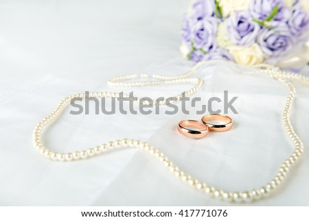 Gold wedding rings lie on a wedding dress. Against the background of the necklace of pearls and wedding bouquet. - stock photo