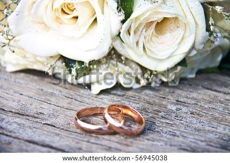 Gold wedding rings on a bouquet of white roses - stock photo