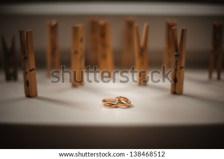 gold wedding rings on a window-sill with the wooden pegs of clothes on a background - stock photo