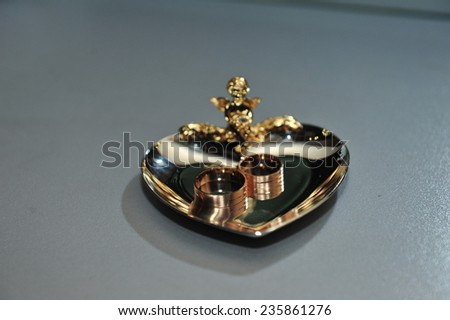 gold wedding rings on the gold plate heart design.  - stock photo