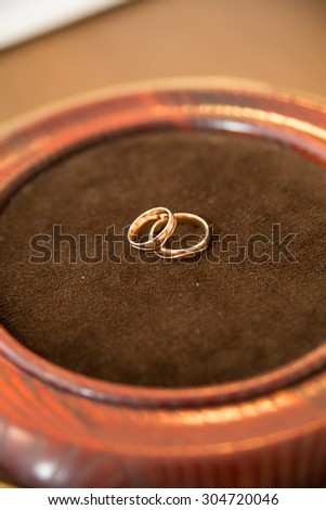 Gold wedding rings on the pincushion. - stock photo