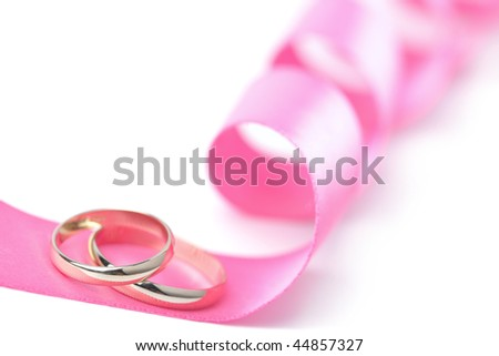 Gold wedding rings over pink ribbon isolated